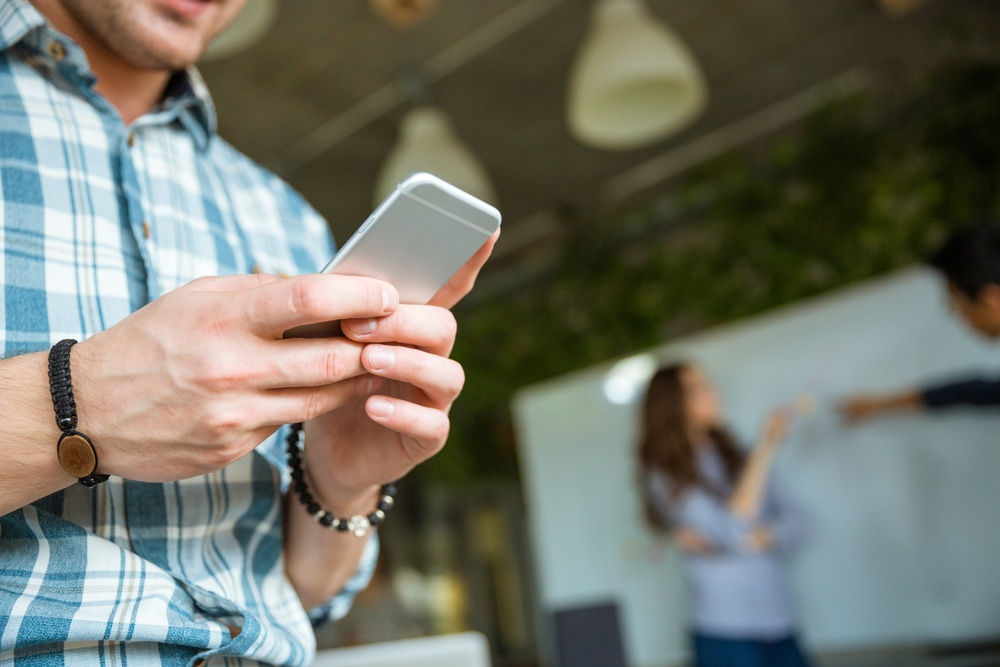 Closeup of hands of young man in checkered shirt using mobile phone while his partners arguing