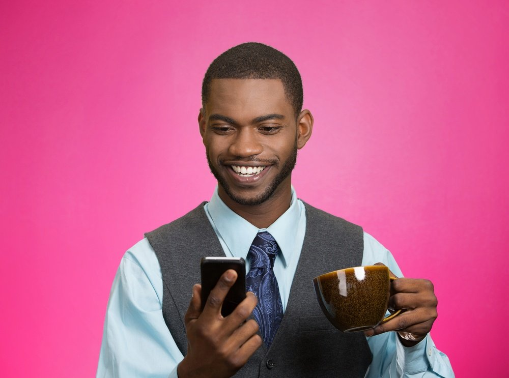 Closeup portrait happy, smiling business man reading good news on smart phone, lawyer holding mobile, drinking cup coffee isolated pink background. Human face expression, emotion, corporate executive