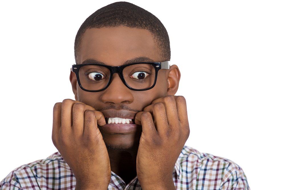 Closeup portrait of young nerdy, unhappy, scared man, student with big glasses biting nails, looking away with a craving for something, anxious, worried, isolated on white background. Face expression