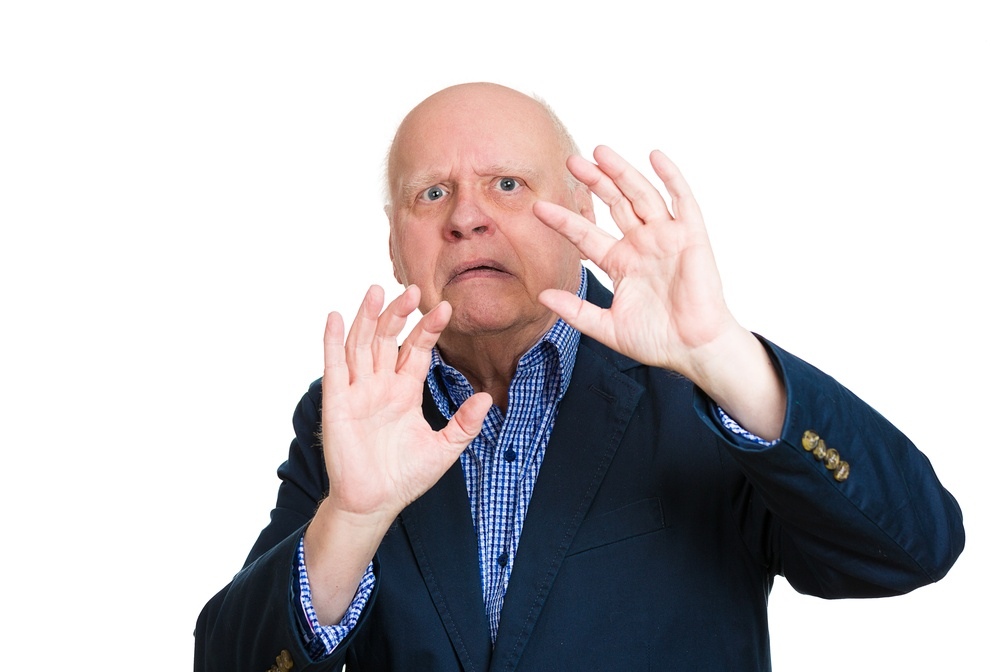 Closeup portrait, senior mature man, looking shocked, scared trying to protect himself in anticipation of unpleasant situation, isolated white background. Negative emotion facial expression feeling