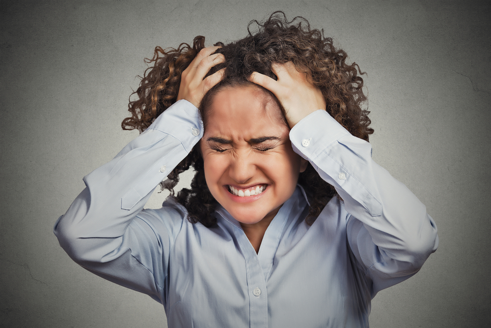 Frustrated stressed young woman. Headshot unhappy overwhelmed girl having headache bad day pulling her hair out isolated on grey wall background. Negative emotion face expression feelings perception