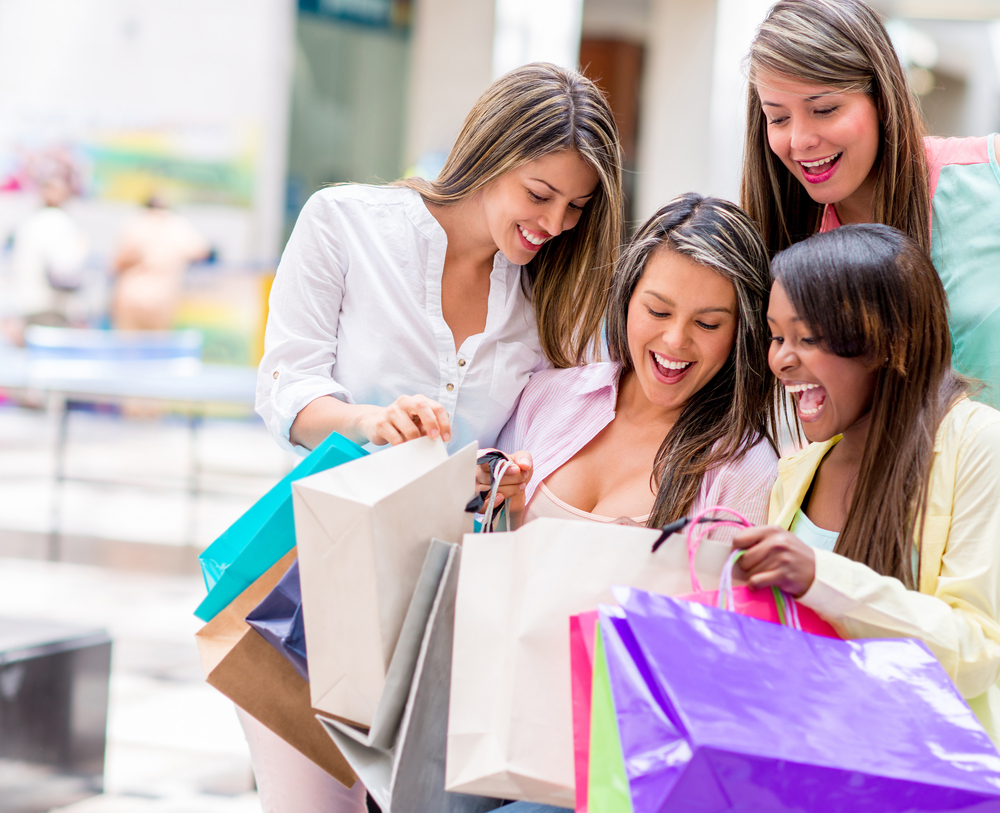 Group of happy shopping women looking in their bags