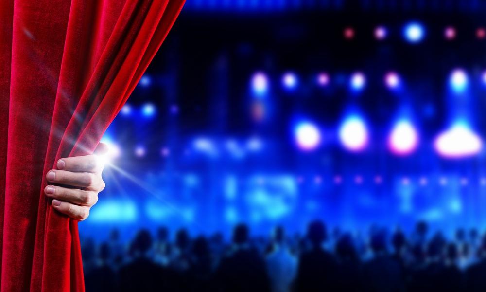 Hand of businessman opening red velvet curtain
