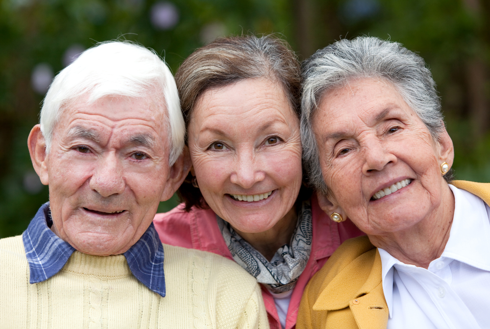 Old couple and their daughter smiling outdoors-1