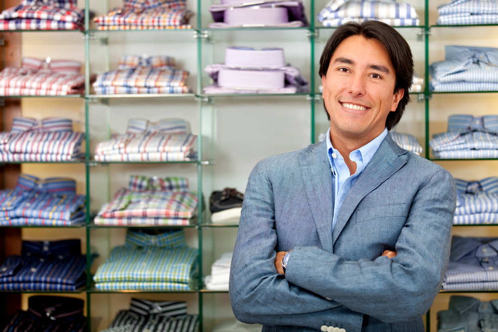 Smiling shop manager in front of tshirts