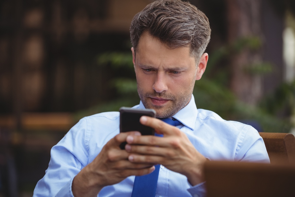 Thoughtful businessman using mobile phone